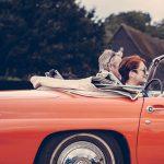 オープンカーでドライブする夫婦